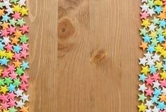 Ram av färgrika godisstjärnor på wood bakgrund fotografering för bildbyråer