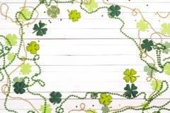 Ram av filtfyrklöver och pärlor på den vita träbackgroen Arkivfoto