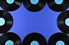 Ram av gamla svarta vinylrekord på blå bakgrund Arkivbild