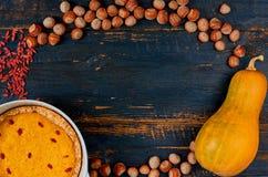 Ram av garnering för tacksägelsepaj eller kaka: pumpa som är syrlig, gojibär, hasselnötter på den svarta träbakgrunden arkivfoton
