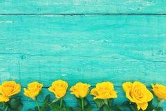 Ram av gula rosor på lantlig träbakgrund för turkos val royaltyfria foton