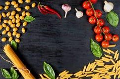 Ram av italiensk traditionell mat, kryddor och ingredienser för att laga mat som basilika, körsbärsröda tomater, chilipeppar, vit royaltyfria bilder