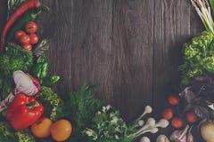 Ram av nya grönsaker på träbakgrund med kopieringsutrymme Arkivfoto
