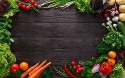 Ram av nya grönsaker på träbakgrund med kopieringsutrymme royaltyfri foto