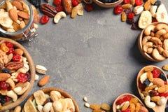 Ram av olika torkade frukter och muttrar på färgbakgrund, bästa sikt arkivfoton