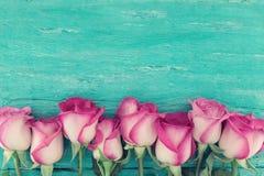Ram av rosa rosor på lantlig träbakgrund för turkos med c Arkivfoto