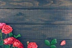 Ram av rosor på mörk lantlig träbakgrund just rained Royaltyfri Fotografi