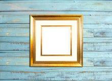 Ram för guldtappningbild på blå wood bakgrund Royaltyfria Foton