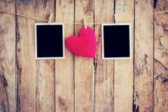Ram för röd hjärta som och för två foto hänger på klädstreckrep med w arkivbilder