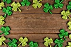 Ram för treklöverer för dag för St Patricks skinande över lantligt trä Fotografering för Bildbyråer