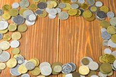 Ram från mynt på träbakgrunds- och kopieringsutrymme för text i mitt bakgrundsbegreppet bantar guld- äggfinans Arkivbild