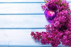 Ram från nya aromatiska lilablommor och den dekorativa stearinljuset Arkivbild