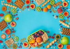 Ram med lunchasken och assorty av frukter, bär och knastranden arkivfoton
