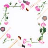 Ram med rosa rosor och kvinnliga skönhetsmedel på vit bakgrund Skönhetbegrepp, kvinnadag Lekmanna- lägenhet, bästa sikt Arkivbild