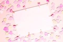 Ram mellanrum, papper för text-, lyckönskan- och kopieringsutrymme på en pastellfärgad rosa bakgrund med små hjärtor, bästa sikt  arkivfoton
