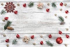 Ram på julbakgrund av gammalt trä Red och guldbaubles branches kottegran Xmas-objekt Top beskådar royaltyfri fotografi