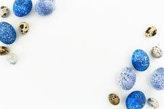 Ram som göras av blåa spräckliga easter ägg och vaktelägg med kopieringsutrymme på vit bakgrund Lekmanna- lägenhet, bästa sikt Fotografering för Bildbyråer