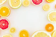 Ram som göras av citrusfrukter på vit bakgrund Lekmanna- lägenhet, bästa sikt Bakgrund för frukt` s Royaltyfri Foto