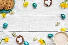 Ram som göras av easter ägg, koppen av cappuccino, vårblommor och kex på vit träbakgrund sammansättning easter Arkivbild