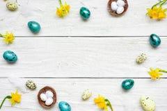 Ram som göras av easter ägg och vårblommor på vit träbakgrund sammansättning easter Royaltyfria Foton