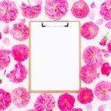 Ram som göras av purpurfärgade rosor, ranunculus och skrivplattan på vit bakgrund Lekmanna- lägenhet, bästa sikt Blom- modell av  Royaltyfri Bild