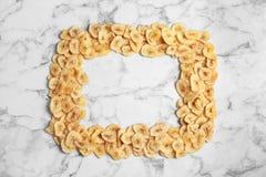 Ram som göras av söta bananskivor på marmorbakgrund, bästa sikt med utrymme för text close 3 torkade upp - frukttyper arkivbilder