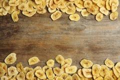 Ram som göras av söta bananskivor på träbakgrund, bästa sikt med utrymme för text arkivbilder