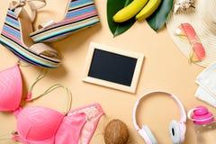 Ram som göras av sommarstrandtillbehör på den gula bakgrunden - swimwear, sandaler, hörlurar, solglasögon, frukter, sugrörhatt, royaltyfri fotografi