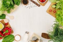 Rama świeża zielona sałatka, czerwona papryka, czereśniowy pomidor, pieprz, olej i kitchenware na miękkiej białej drewnianej desc Zdjęcia Royalty Free