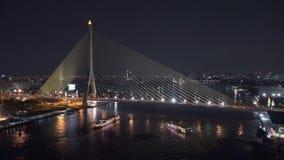 Rama 8 Bridge, suspension bridge crossing Chao Phraya River in Bangkok city at night, Thailand. 4K cityscape VDO. stock footage