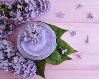 Rama cosmética poner crema del cuidado de la lila de la regeneración en la armonía de madera rosada que hidrata Imagen de archivo