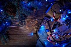 Rama de árbol de abeto con las luces de la Navidad, la caja de regalo y los bastones de caramelo en fondo de madera con el espaci Imagen de archivo libre de regalías