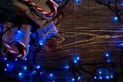 Rama de árbol de abeto con las luces de la Navidad, la caja de regalo y los bastones de caramelo en fondo de madera con el espaci Fotografía de archivo