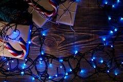 Rama de árbol de abeto con las luces de la Navidad, la caja de regalo y los bastones de caramelo en fondo de madera con el espaci Fotografía de archivo libre de regalías