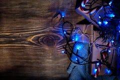 Rama de árbol de abeto con las luces de la Navidad, la caja de regalo y los bastones de caramelo en fondo de madera con el espaci Fotos de archivo libres de regalías