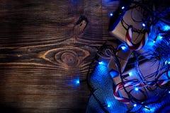 Rama de árbol de abeto con las luces de la Navidad, la caja de regalo y los bastones de caramelo en fondo de madera con el espaci Foto de archivo