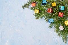 Rama de árbol de abeto de la Navidad con los pequeños regalos en fondo azul Copie el espacio Fotografía de archivo libre de regalías