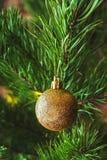Rama de árbol de navidad con la bola de oro Fotos de archivo