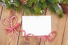 Rama de árbol de navidad y tarjeta de felicitación en blanco Fotografía de archivo