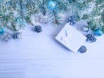 Rama de árbol, decorativo estacional del diseño del regalo de la bola en el fondo de madera blanco, nieve foto de archivo