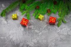 Rama de árbol de navidad con un juguete en un fondo gris Imágenes de archivo libres de regalías