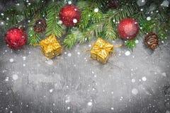 Rama de árbol de navidad con un juguete en un fondo gris Fotografía de archivo libre de regalías