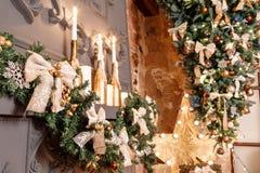Rama de árbol de navidad en la chimenea y otras decoraciones del día de fiesta en desván oscuro Fotografía de archivo
