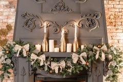 Rama de árbol de navidad en la chimenea y otras decoraciones del día de fiesta en desván oscuro Foto de archivo libre de regalías