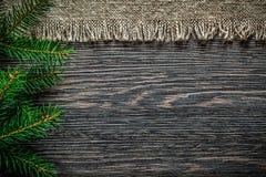 Rama de la piel de la arpillera del vintage en fondo de la Navidad del tablero de madera fotografía de archivo libre de regalías