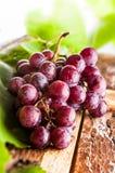 Rama de las uvas en el tablero de madera Imagenes de archivo