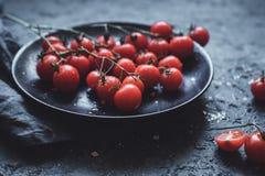 Rama de los tomates de cereza en la placa negra, cierre para arriba Foco selectivo fotos de archivo