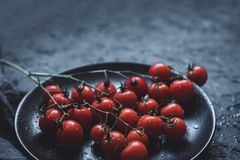 Rama de los tomates de cereza maduros en la placa negra, cierre para arriba Con el espacio de la copia fotos de archivo libres de regalías