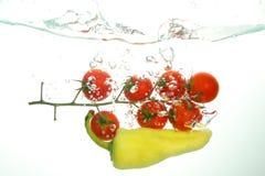 Rama de los tomates de cereza rojos y del papper verde bajo spash del agua foto de archivo