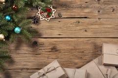 Rama de un árbol de navidad con los juguetes en superficie de madera Fotos de archivo